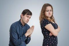 Den unga mannen tigger för ung ilsken kvinna för förlåtelse arkivfoton