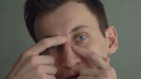 _ Den unga mannen trycker på en finne framme av en spegel lager videofilmer