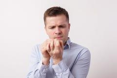 Den unga mannen undersöker försiktigt spikar dålig nagelbitningspänning arkivfoton