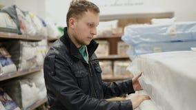 Den unga mannen väljer en madrass i ett stort möblemang shoppar eller supermarket Han kontrollerar dess spänst, minnesskum förbi arkivfilmer
