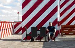 Den unga mannen vilar sammanträde på en tabell i ett kafé Royaltyfria Foton