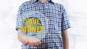 Den unga mannen visar att ett hologram av planetjorden och text sparar pengar Royaltyfria Bilder
