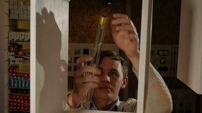 Den unga mannen vrider den Edison kulan i lampformgivaren Tappninglampa med långa trådar av glödtråden Härligt varmt ljus arkivfilmer