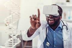 Den unga medicinska arbetaren som bär VR, rullar med ögonen på arbete Royaltyfri Bild