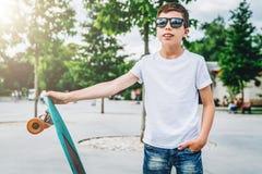 Den unga millennial t-skjortan för iklädd vit för pojken är utomhus- ställningar Åtlöje upp Utrymme för logoen, text, bild fotografering för bildbyråer
