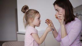 Den unga modern gör gyckel med hennes lilla dotter på köket Gör sig exponeringsglas från baglar och att le och gör lager videofilmer