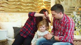 Den unga modern kammar hennes litet barndotterhår, och fadern sitter bredvid arkivfilmer