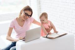 Den unga modern med behandla som ett barn att arbeta och att använda bärbara datorn royaltyfri foto