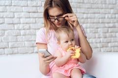 Den unga modern med litet behandla som ett barn genom att använda smartphonen royaltyfria foton