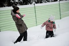 Den unga modern och dottern har gyckel i snowen Fotografering för Bildbyråer