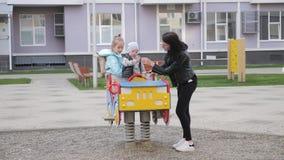Den unga modern och hennes två barn på lekplatsen, har roligt, livsstil arkivfilmer