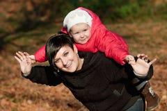 Den unga modern och hon litet barnflickan har gyckel Arkivbilder