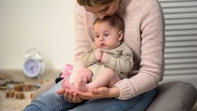 Den unga modern som beundrar mycket små ben för söner, behandla som ett barn att sitta på kvinnans varv, lycka arkivbild