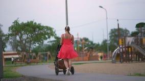 Den unga modern som går barnvagn i stad, parkerar anseendet som bär den ljusa röda klänningen med nakna ben lager videofilmer