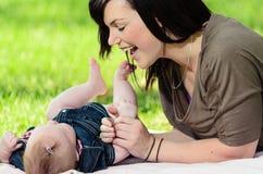 Den unga modern som leker med, behandla som ett barn Royaltyfria Bilder
