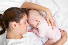 Den unga modern som omfamnar henne som sovar, behandla som ett barn Arkivbild