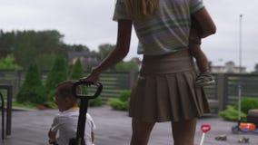 Den unga modern som spelar och har gyckel med hennes, behandla som ett barn pojkesonbröder i en grön trädgård med bilar - varma f arkivfilmer