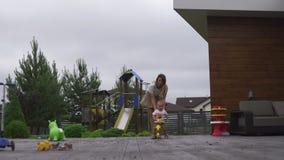 Den unga modern som spelar och har gyckel med hennes, behandla som ett barn pojkesonbröder i en grön trädgård med cyklar - varma  arkivfilmer