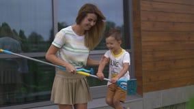 Den unga modern som spelar och har gyckel med hennes, behandla som ett barn pojkesonbröder i en trädgård med leksaker - varm färg lager videofilmer