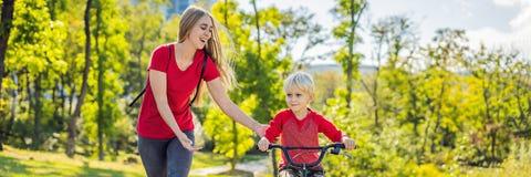 Den unga modern som undervisar hennes son hur man rider en cykel i, parkerar BANRET, LÅNGT FORMAT royaltyfri foto