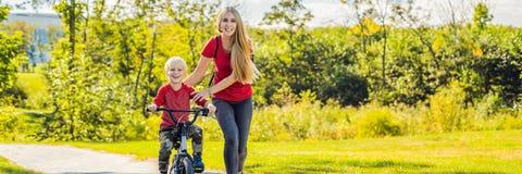 Den unga modern som undervisar hennes son hur man rider en cykel i, parkerar BANRET, LÅNGT FORMAT royaltyfri fotografi