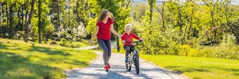 Den unga modern som undervisar hennes son hur man rider en cykel i, parkerar BANRET, LÅNGT FORMAT royaltyfria foton