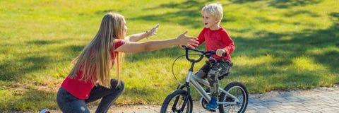 Den unga modern som undervisar hennes son hur man rider en cykel i, parkerar BANRET, LÅNGT FORMAT arkivbild