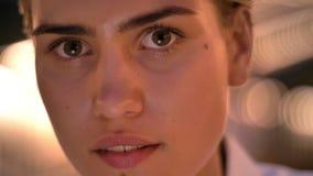 Den unga moderna kvinnan sitter på stege och att hålla ögonen på i minnestavla i aftonen som håller ögonen på på kameran, suddiga arkivfilmer