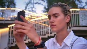Den unga moderna kvinnan står på bron, tar fotoet av solnedgången på smartphonen, överför den, kommunikationsbegreppet, stege stock video
