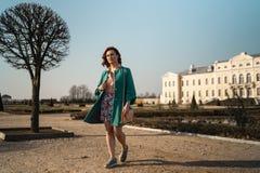 Den unga modevänkvinnan som waling i, parkerar det bärande livliga gröna omslaget och en färgrik kjol royaltyfria foton