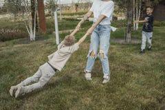 Den unga mumen som omkring v?nder och att virvla med hennes s?ner p?, parkerar lycklig begreppsfamilj royaltyfri foto