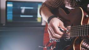 Den unga musikern komponerar och antecknar filmmusiken som spelar gitarren genom att använda datoren och tangentbordet Royaltyfria Foton