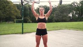 Den unga muskulösa kvinnan gör övningar med skivstången stock video
