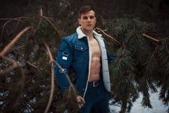 Den unga muskulösa mannen i knäppt upp omslag med gör bar bröstställningar bredvid sörjer trädet i vinterskog royaltyfri bild