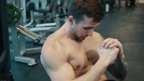 Den unga muskulösa mannen utbildar buk- muskler genom att använda övningsbollen stock video