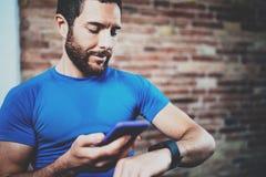Den unga muskulösa stiliga idrottsman nen som kontrollerar sporten, resulterar på smartphoneapplikation och ilar klockan efter br fotografering för bildbyråer