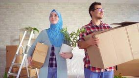 Den unga muslim familjen flyttade sig i en ny lägenhet arkivfilmer