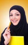 Den unga muslimkvinnan med boken på vit Royaltyfria Bilder