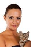 Den unga nätt kvinnan rymmer henne den älskvärda katten isolerad Royaltyfria Bilder