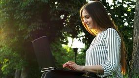 Den unga nätta affärskvinnan som skriver på en bärbar dator som sitter på gräset nära träd, kvinnabruksanteckningsboken i, parker lager videofilmer