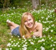 Den unga nätta blonda kvinnan på en äng blommar Royaltyfri Fotografi