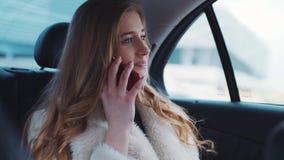Den unga nätta blonda kvinnan sitter samtal på hennes telefon i hennes splitterny bil med moderna insida- och läderplatser och stock video