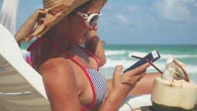 Den unga nätta brunettkvinnan som bär solglasögon och hatten på en dagdrivare, använder mobiltelefonen Arkivbilder