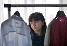 Den unga nätta brunettkvinnan väljer kläder från hängare arkivbilder