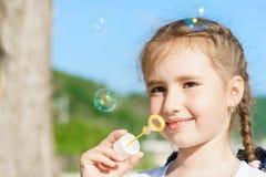 Den unga nätta europeiska ungeflickan med gulligt leende blåser bubblor i utomhus- under-blå himmel på den soliga dagen royaltyfria bilder