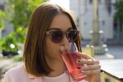 Den unga nätta flickan dricker en kall dryck som är utomhus- Arkivbild