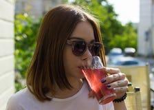 Den unga nätta flickan dricker en kall dryck som är utomhus- Royaltyfri Bild