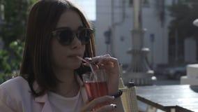 Den unga nätta flickan dricker en kall dryck som är utomhus- stock video