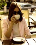 Den unga nätta flickan dricker en kopp av den varma drycken som är utomhus- Arkivbild