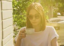 Den unga nätta flickan dricker en kopp av den varma drycken som är utomhus- Royaltyfri Bild